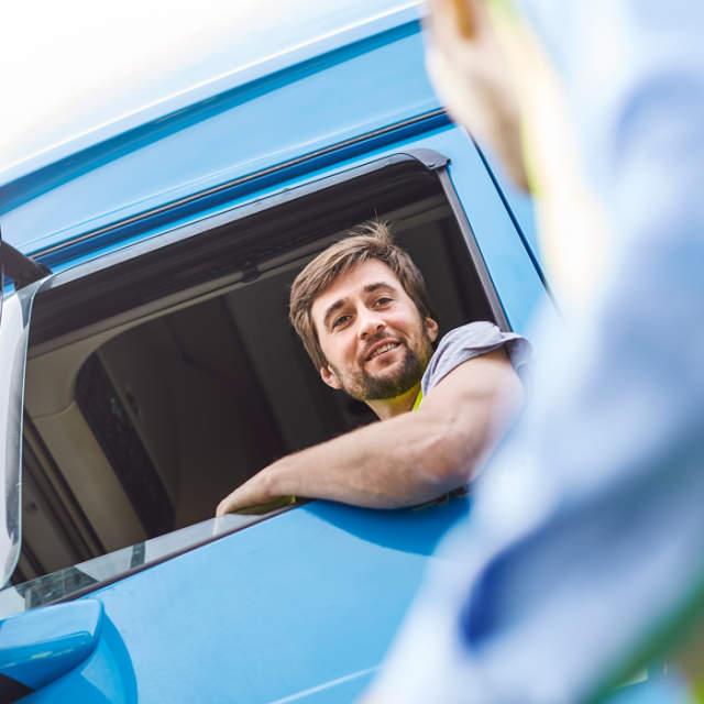 Motorista de camião a entregar paletes de plástico da CHEP para a primeira milha