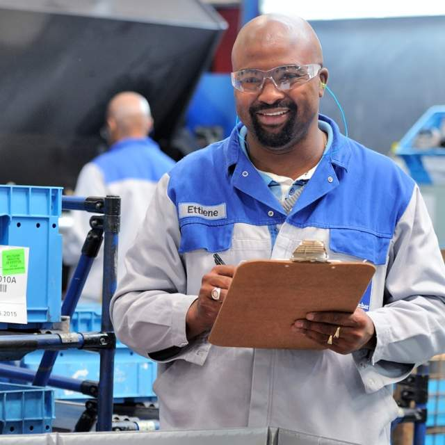 man in factory with clipboard